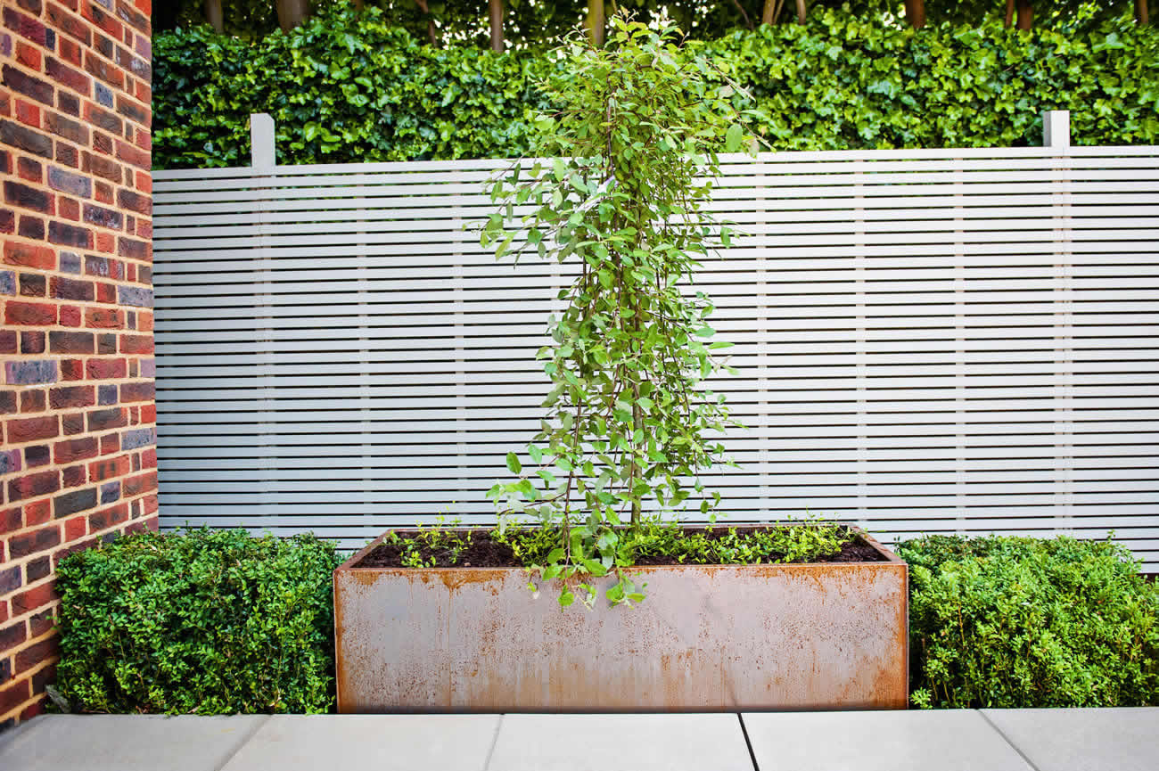 Large garden using portland stone and steel planters in for Garden wall designs ideas