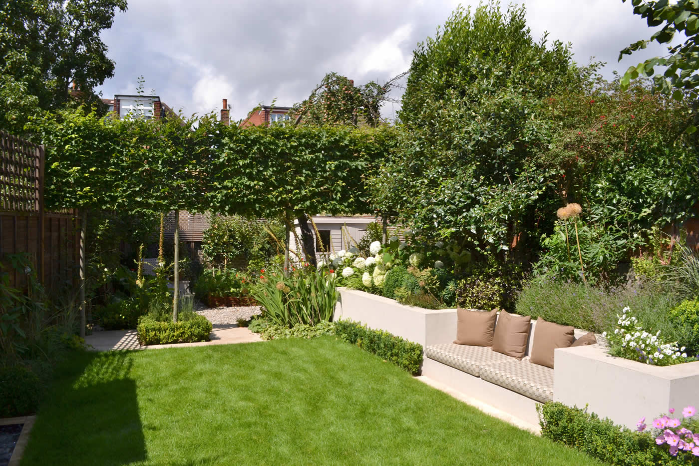 Lovely low maintenance family garden with raised bed for herbs and pl