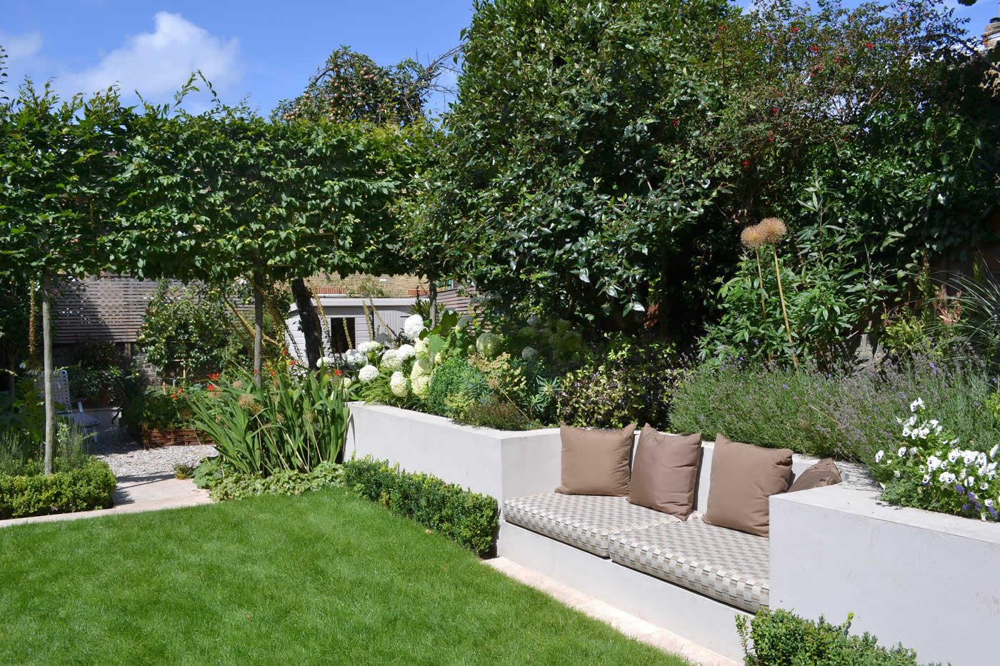 Lovely low maintenance family garden with raised bed for for Family garden designs