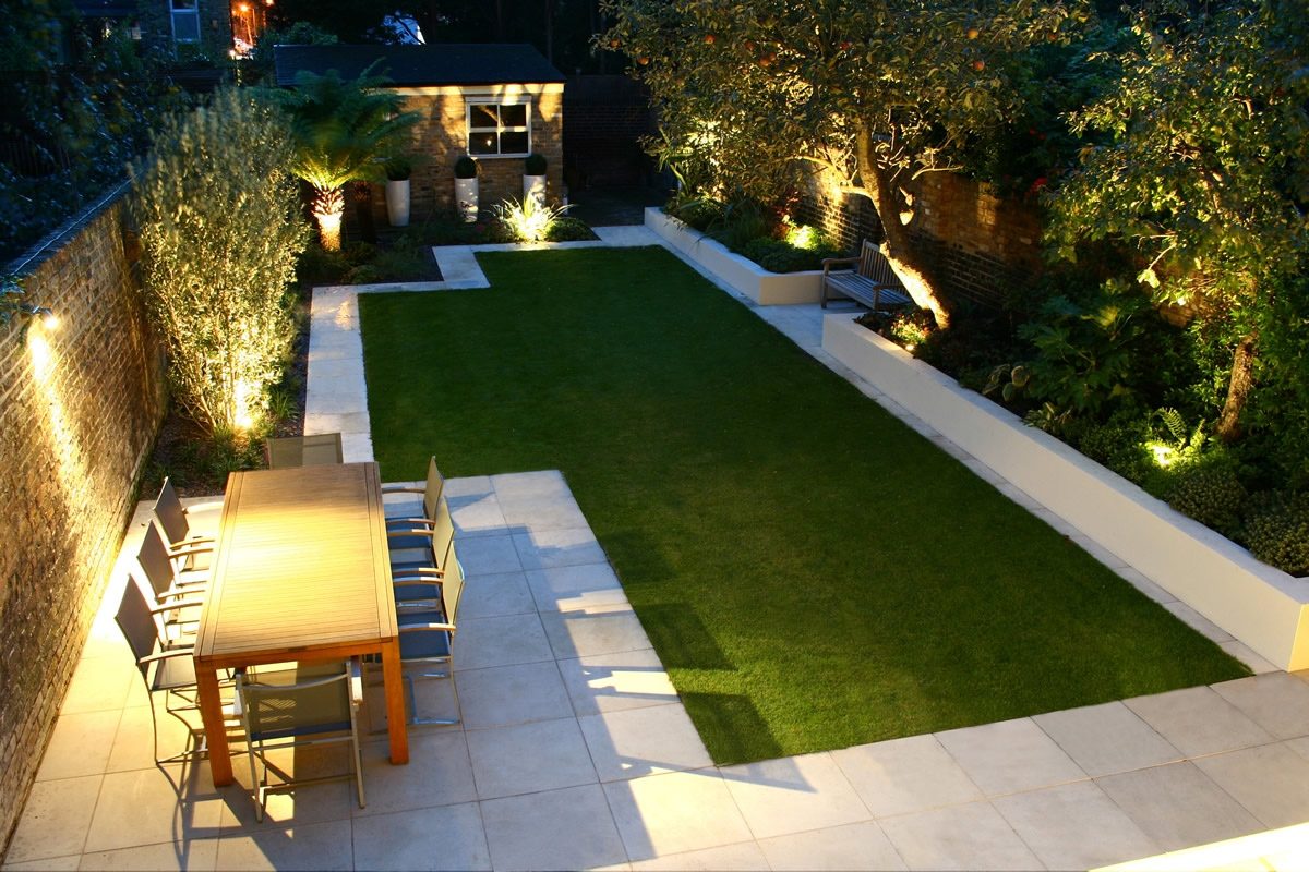Modern family garden in battersea with patio lighting planting and machined sandstone pathway