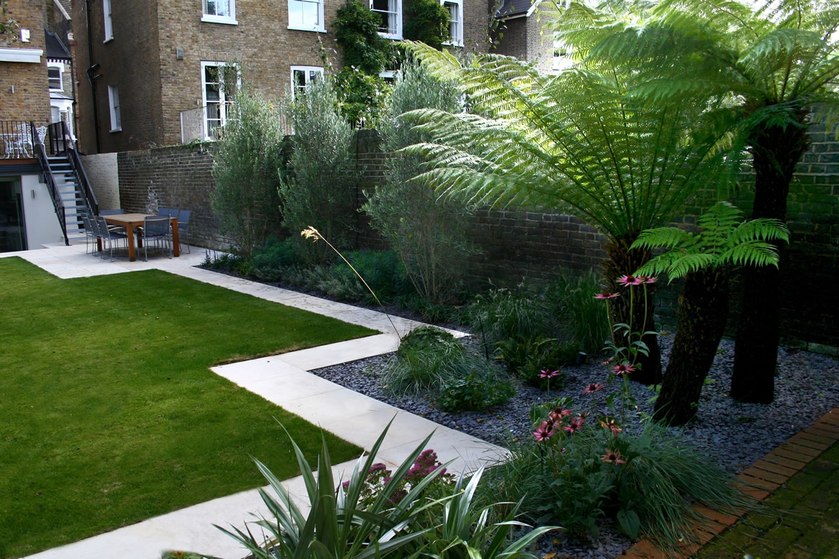 Modern family garden in Battersea with patio lighting planting